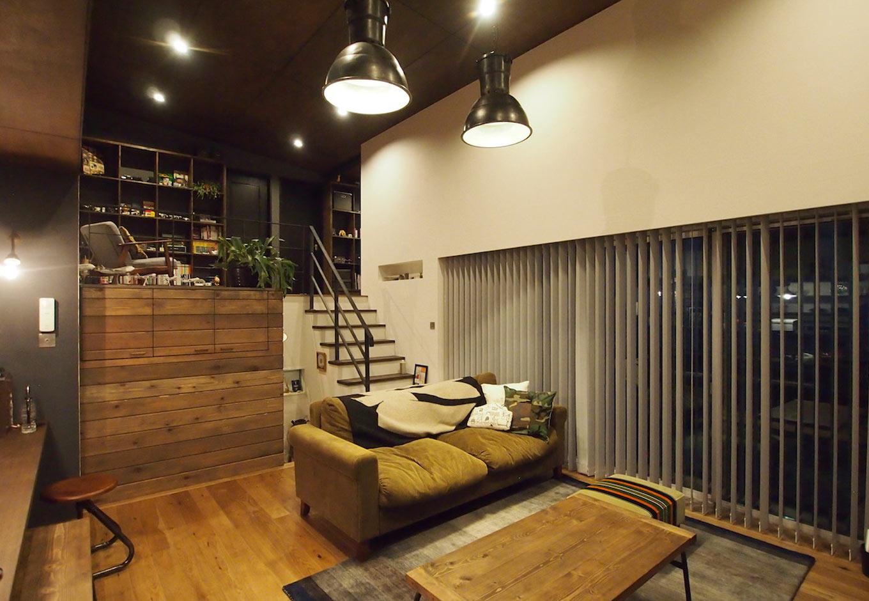 中2階に位置するリビングは天井が高く、階段を上がれば本棚のあるフリースペースへと続くスキップフロアに。オークの床材と天井の板張り、漆喰塗りの壁が落ち着いた雰囲気。アイアンの階段手すりや天井からぶら下がっているビンテージ照明がかっこいい