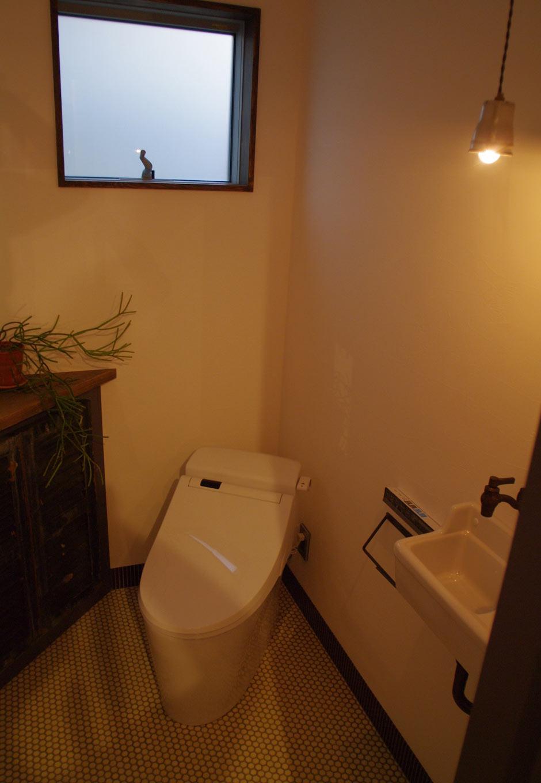 レトロな露出水栓の手洗いやビンテージの小窓を収納扉にアレンジしたり、タンクレストイレを斜め置きにして空間を楽しく演出している