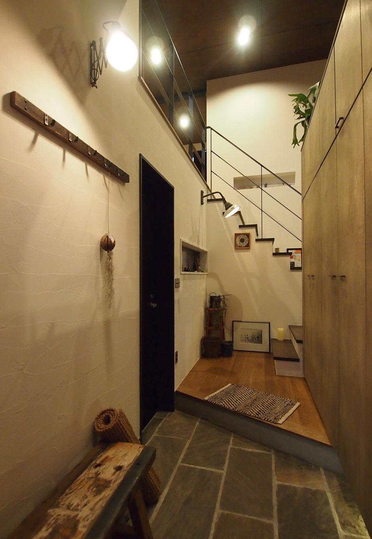 リビングから階段を降りると玄関ホールに続く。玄関ホールには靴はもちろん、アウター類もしまえる壁面収納が。反対側にはビルトインガレージに続く入り口がある