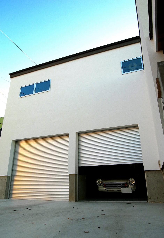 敷地の高低差を利用し、低いところにビルトインガレージを配置、その2階を居室にしている。シャッターは電動なので出入りもスムーズ。雨の日は特に便利。外壁は漆喰塗りで汚れにくく、とても美しい