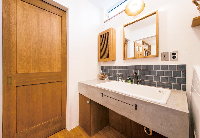 CLASSICA HOME/クラシカホーム【デザイン住宅、夫婦で暮らす、インテリア】洗面台はモルタルで特別に造作して、壁にはタイル張りを採用した。キッチンを中心に、洗面・脱衣室、風呂、トイレ、玄関、LDKと、コンパクトに周遊できる動線の工夫も