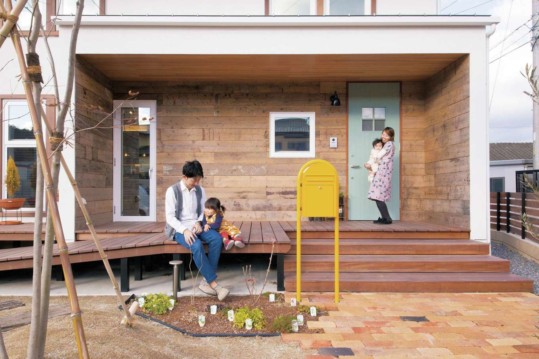 共感住宅 ray-out (レイアウト)【デザイン住宅、子育て、趣味】ウッドデッキで日向ぼっこ。足場板を貼った外観に淡いグリーンの扉が映える