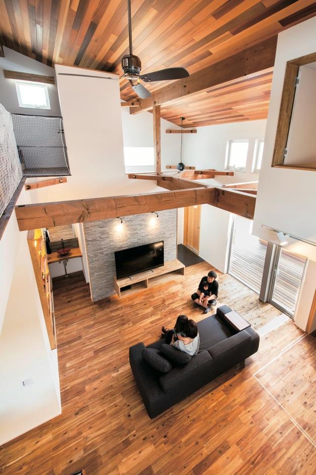 共感住宅 ray-out (レイアウト)【デザイン住宅、自然素材、省エネ】2階ホールから眺めたLDKの風景。木目が美しい床、梁、天井の空間に、大きなシーリングファンが存在感を放つ