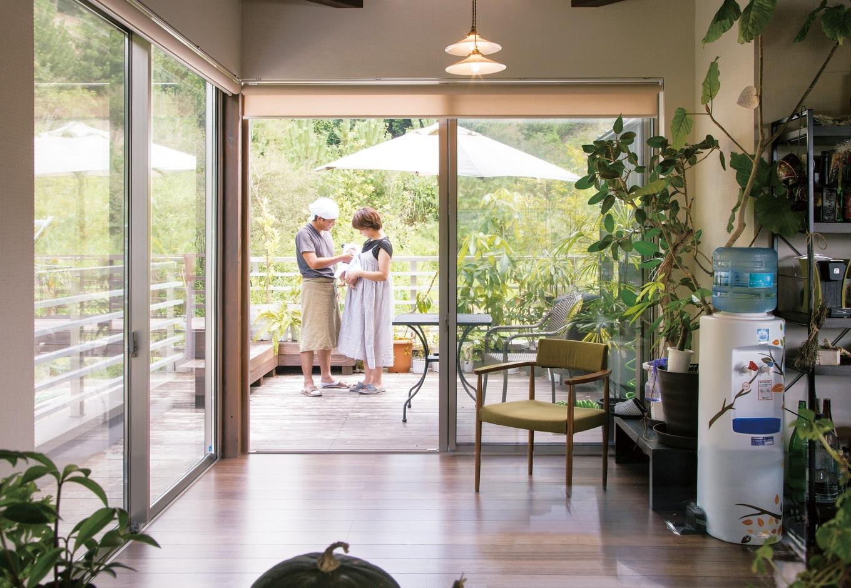 共感住宅 ray-out (レイアウト)【デザイン住宅、趣味、自然素材】大きく窓が開く2階LDKとデッキは段差なくつながり、裏山へと自由に行き来できる。その裏山では野菜や果物を育て、とれたての食材が毎日の食卓に並ぶそうだ