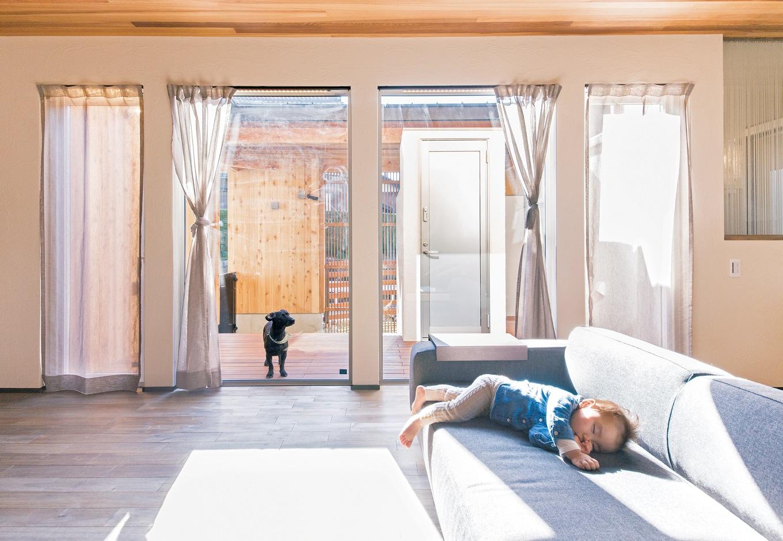 共感住宅 ray-out (レイアウト)【デザイン住宅、自然素材、省エネ】大きな窓から入る暖かい陽光に、女の子はスヤスヤお 昼寝。LDKからは段差無くデッキがつながる