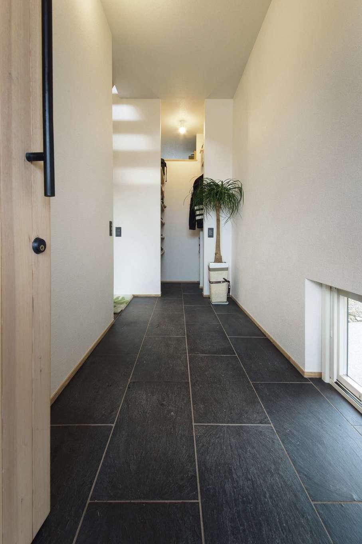共感住宅 ray-out (レイアウト)【デザイン住宅、自然素材、ペット】土間とフロアの段差を無くしてフラットにした玄関。土間の奥にはクロークがある