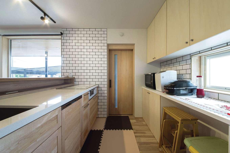 共感住宅 ray-out (レイアウト)【デザイン住宅、自然素材、ペット】キッチンのナチュラルな木目とサブウェイタイルがベストマッチ。正面のドアの先はパントリー。食品を保管するため、室内の全館空調の暖かさが伝わらない造りにしてある
