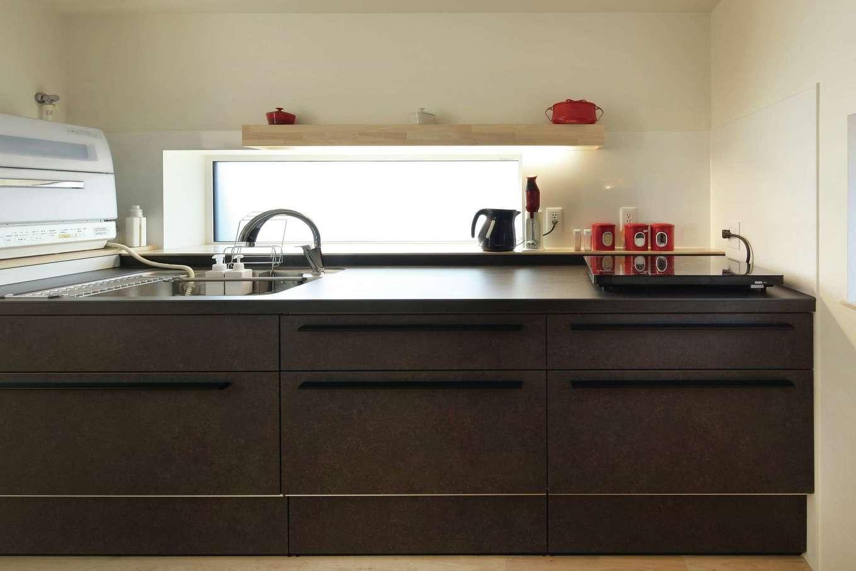 ダークトーンのキッチンは赤い小物と窓から刺す光がアクセント。IH調理器は施主さんの要望で使わない時には片付けられる外付けの物に