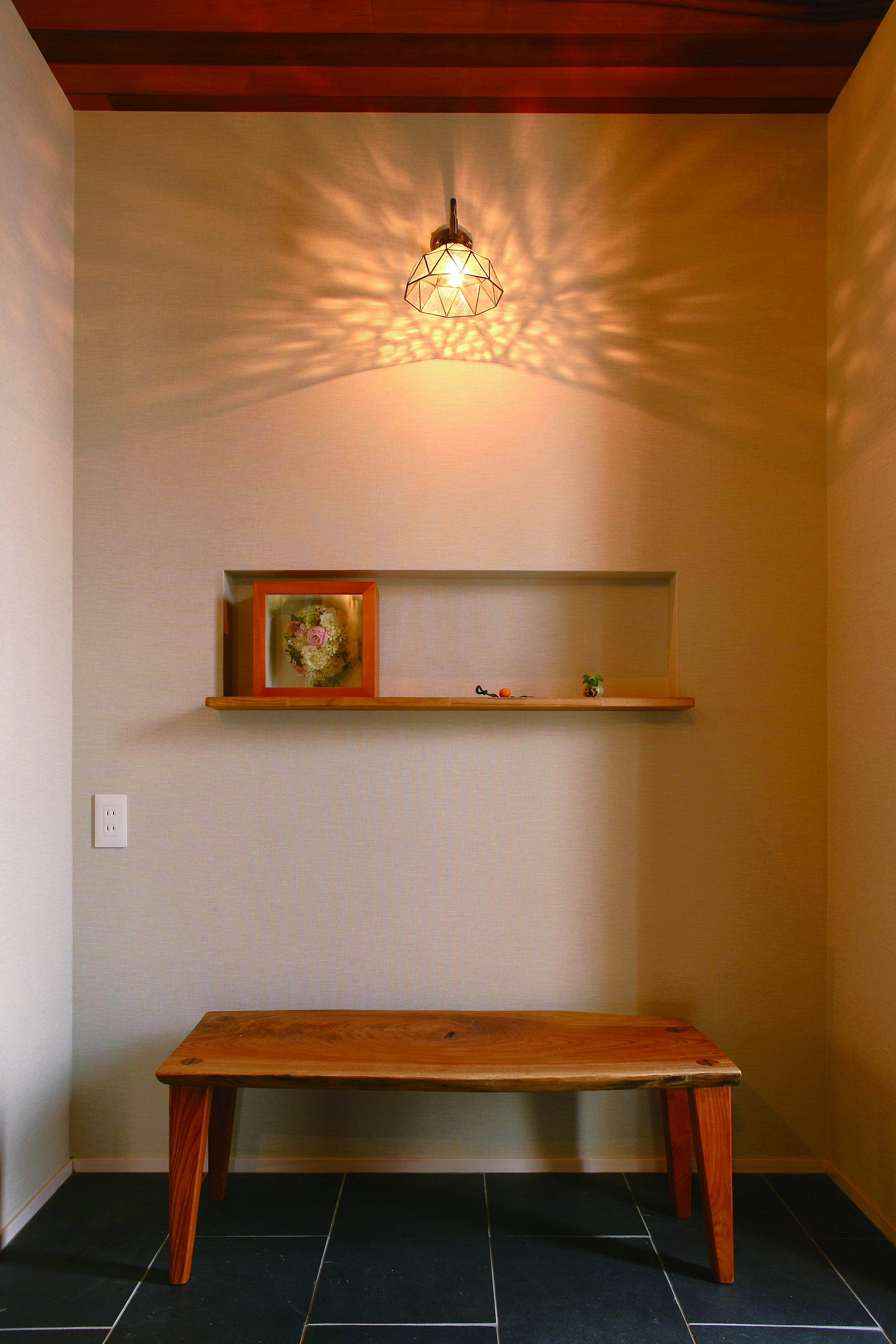 共感住宅 ray-out (レイアウト)【デザイン住宅、子育て、趣味】優しい光が彩る玄関には調和の取れたデザインのベンチを設置