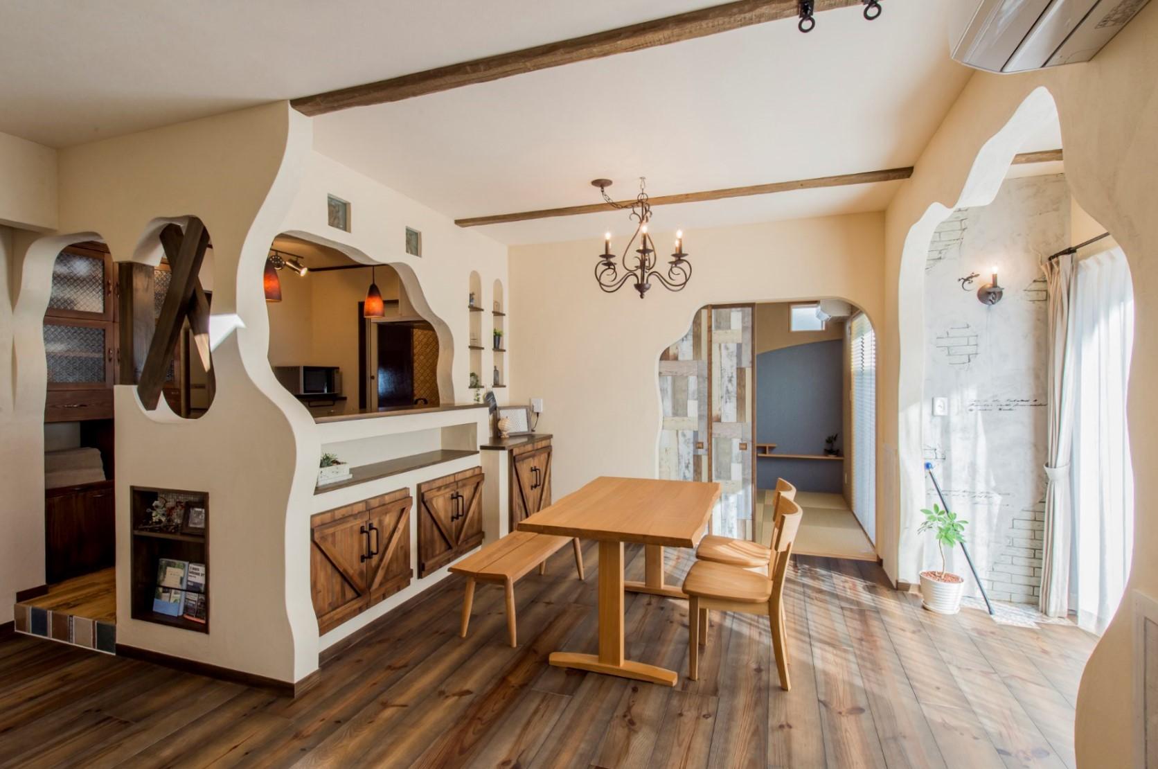 つくし工房【デザイン住宅、趣味、自然素材】自然素材に囲まれた温かみあるLDK。曲線で描かれた塗り壁に、『つくし工房』オリジナルの食器棚、室内扉がよく馴染む。床材や腰壁はエイジング加工をし、遊び心のあるアンティーク感を演出している