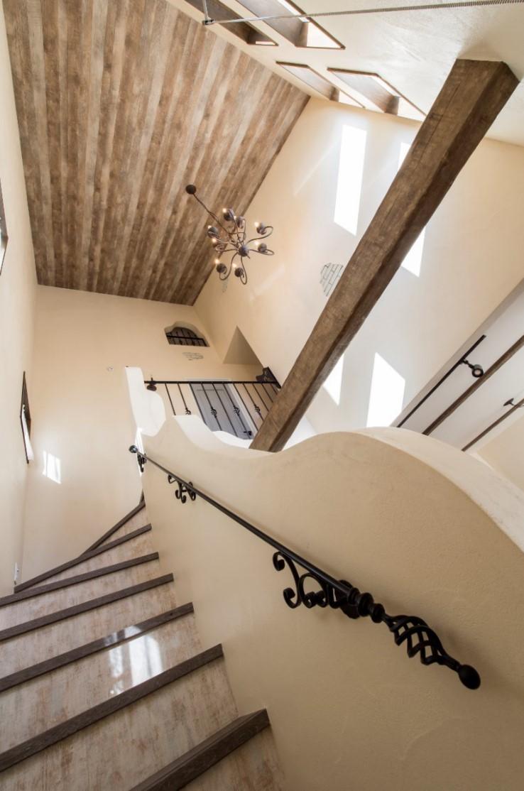つくし工房【デザイン住宅、趣味、自然素材】階段は吹き抜けのようなつくりで開放感抜群。アイアン手すりやモルタル造形も全て手づくりの空間に、シャンデリアがよく似合う