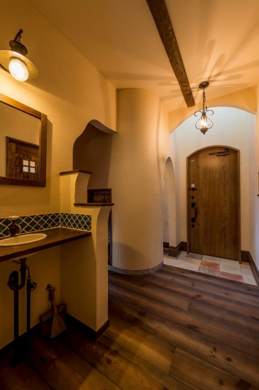 つくし工房【デザイン住宅、趣味、自然素材】まるで絵本の中に入ったような雰囲気のある玄関には、外から帰ってきたらすぐに手を洗える位置に洗面台を設置。アール型の垂れ壁や照明雑貨がかわいい。