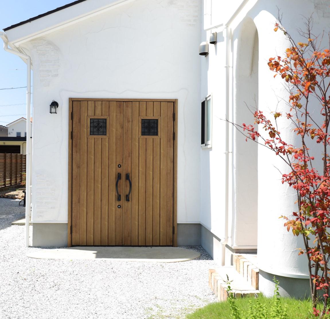 つくし工房【デザイン住宅、趣味、自然素材】木製ドアがかわいいガレージ。ご主人の趣味グッズが格納されている
