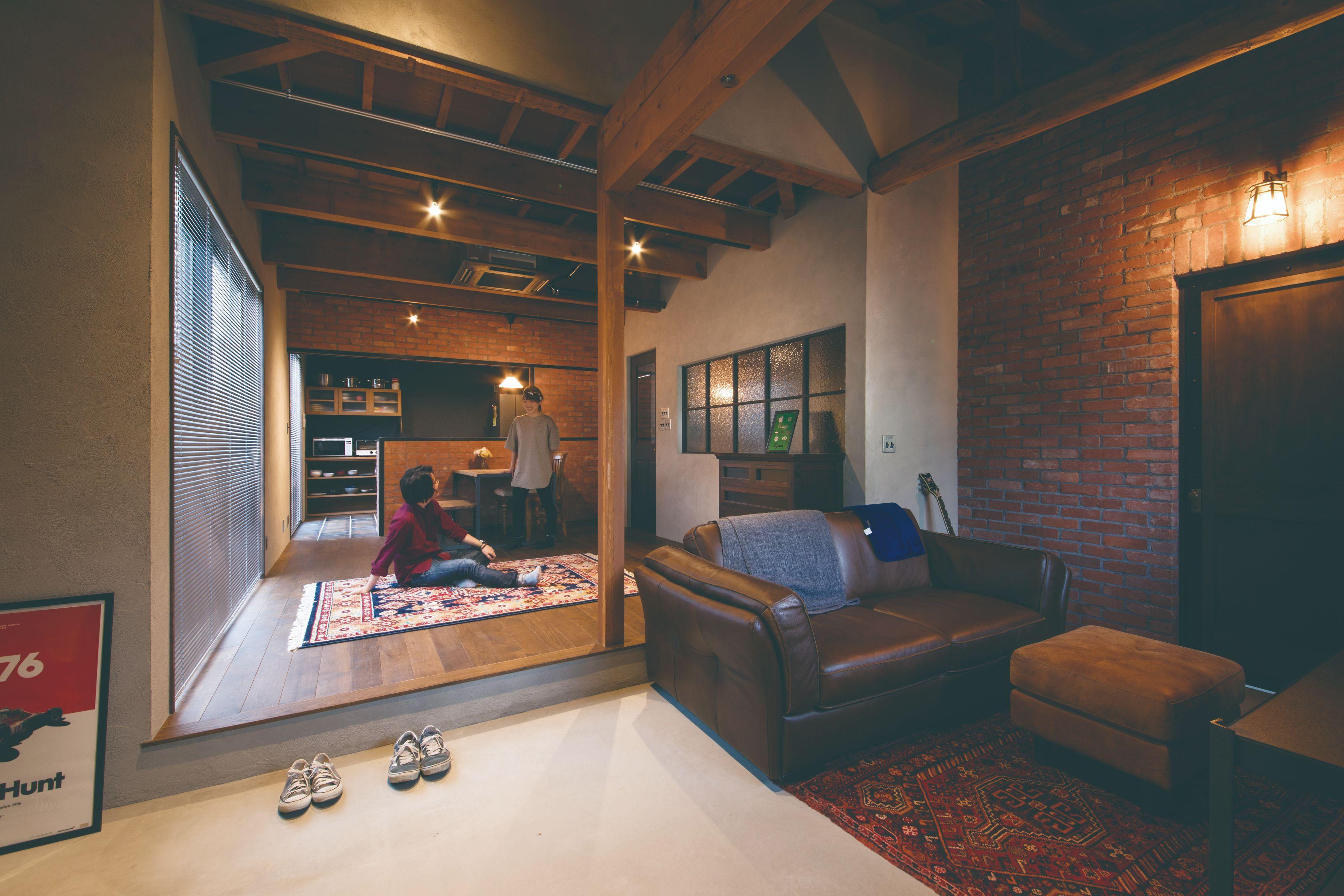 玄関を入った瞬間、外観との大きなギャップに誰もが驚かされる。古い柱と梁を活かしつつ、赤レンガと土間を組み合わせた空間をヴィンテージ家具や照明でコーディネートした