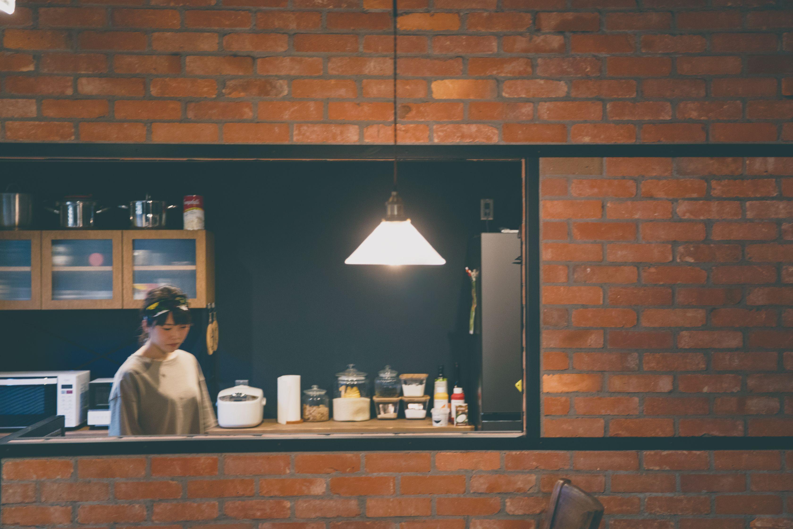 アンティークカフェっぽく仕上げたオープンキッチン。レトロなペンダントライトが赤レンガによく似合う