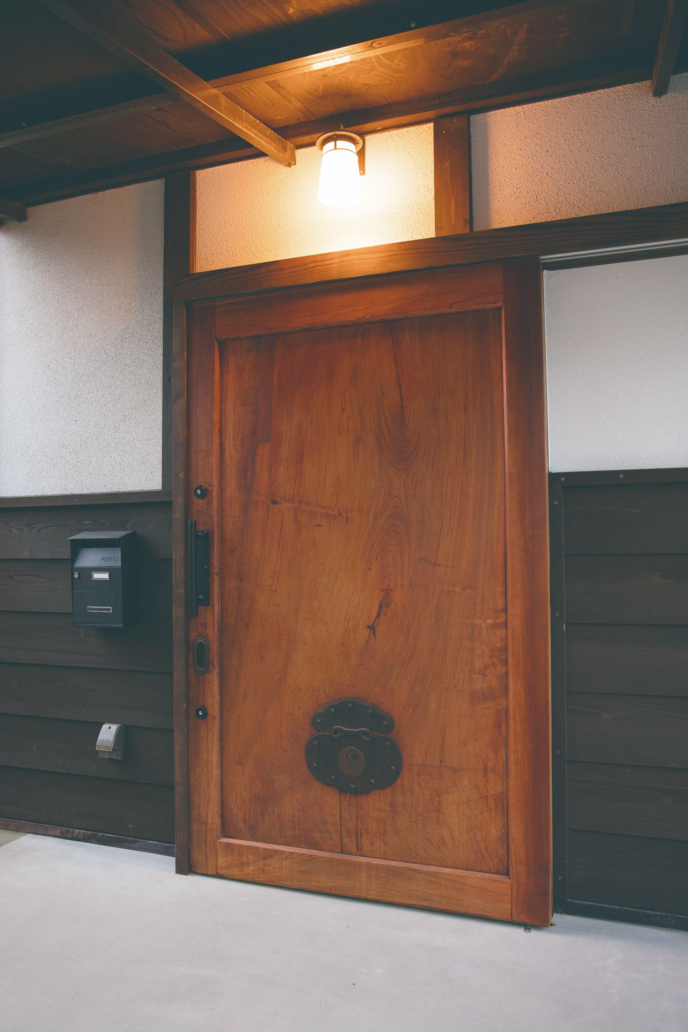 ケヤキの一枚板で造られた200年前の蔵戸を玄関扉に使用