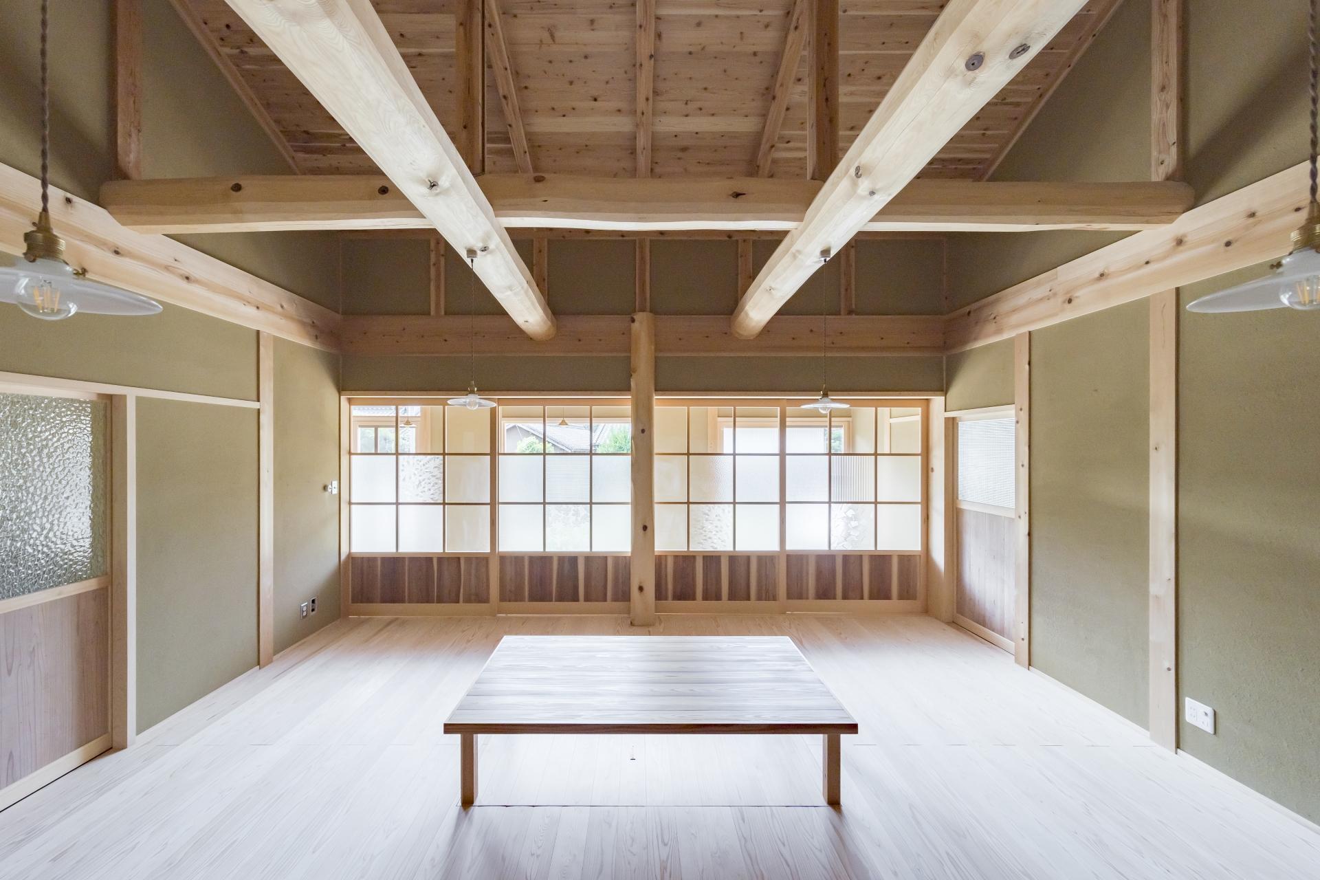 WOODLIFE style 丸守木材【子育て、自然素材、平屋】リビングに寝転がると、趣のある丸太組みの天井が、仕事の疲れや時間を忘れさせてくれる。レトロな建具は建具職人さんの手作り。ガラスもこだわりの1枚