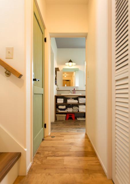 MinerBaseStudio/ミネルベーススタジオ【デザイン住宅、輸入住宅、趣味】玄関から右手にリビング、左手に2階への階段、正面に洗面と生活動線も考えられた設計。ライトグリーンの扉もアクセントに