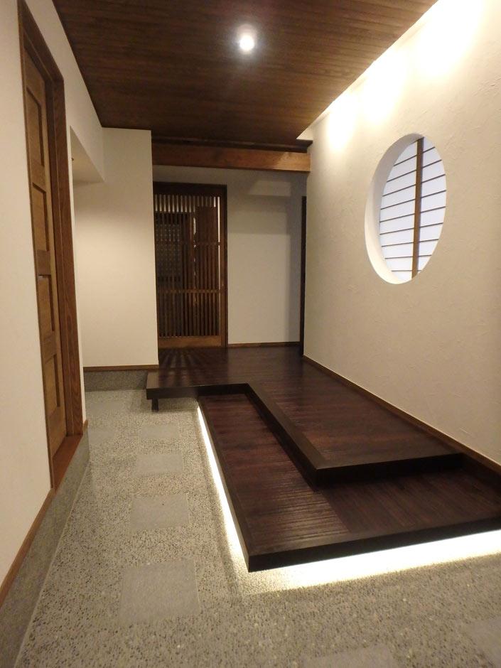 床に使用した栗の木材と足元から柔らかな光を放つ間接照明、丸窓とが溶け合い、品のある玄関になっている