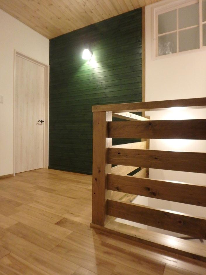 2階ホールは、奥さまのセンスが光る深いグリーンの壁で変化をつけ、間接照明が広々とした空間を暖かく照らす