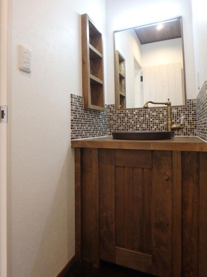 モザイクタイルが目を引く造作洗面台はアンティーク調の水栓を使用し、細かい部分にまでこだわりが。壁を使った収納でコンパクトながらも機能性に優れている