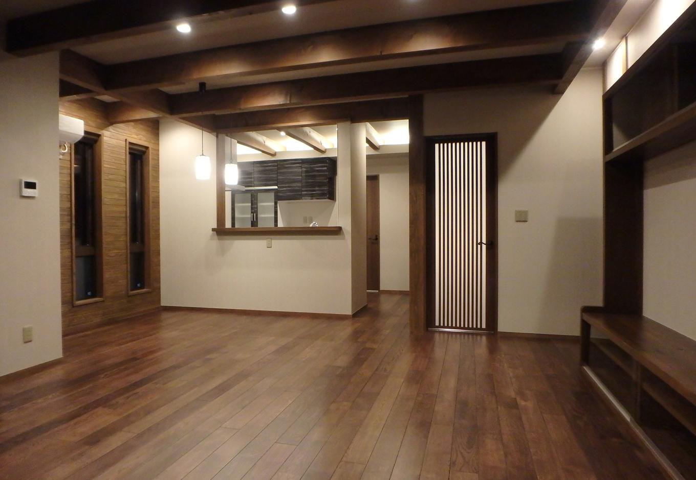 梁が特徴的なリビングはTVボードを家全体の雰囲気に統一するよう造作。奥のキッチンからリビングを見ることができ、料理をしている奥さんも安心