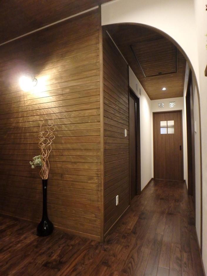 アールが掛かった壁に繋がる廊下は自然素材をふんだんに使い、落ち着いた雰囲気に
