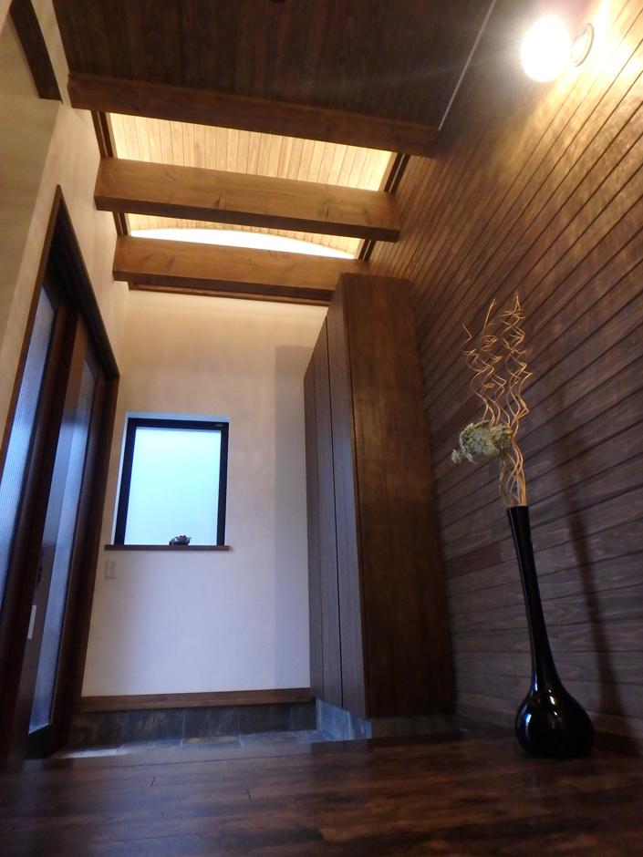 玄関天井には梁と間接照明が客人を優しく迎え入れてくれる