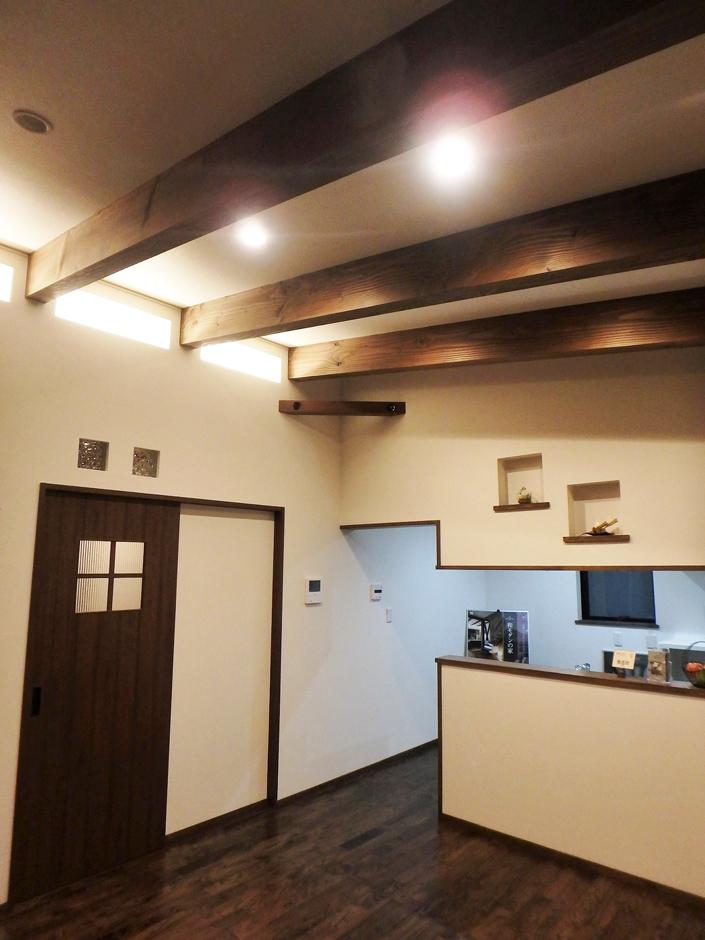 TDホーム静岡西 ウエストンホームズ【デザイン住宅、自然素材、平屋】リビングには大きな梁と勾配天井があり、空間にメリハリを印象付ける。キッチン側の壁にはニッチ、ドアにはステンドガラスが可愛らしい