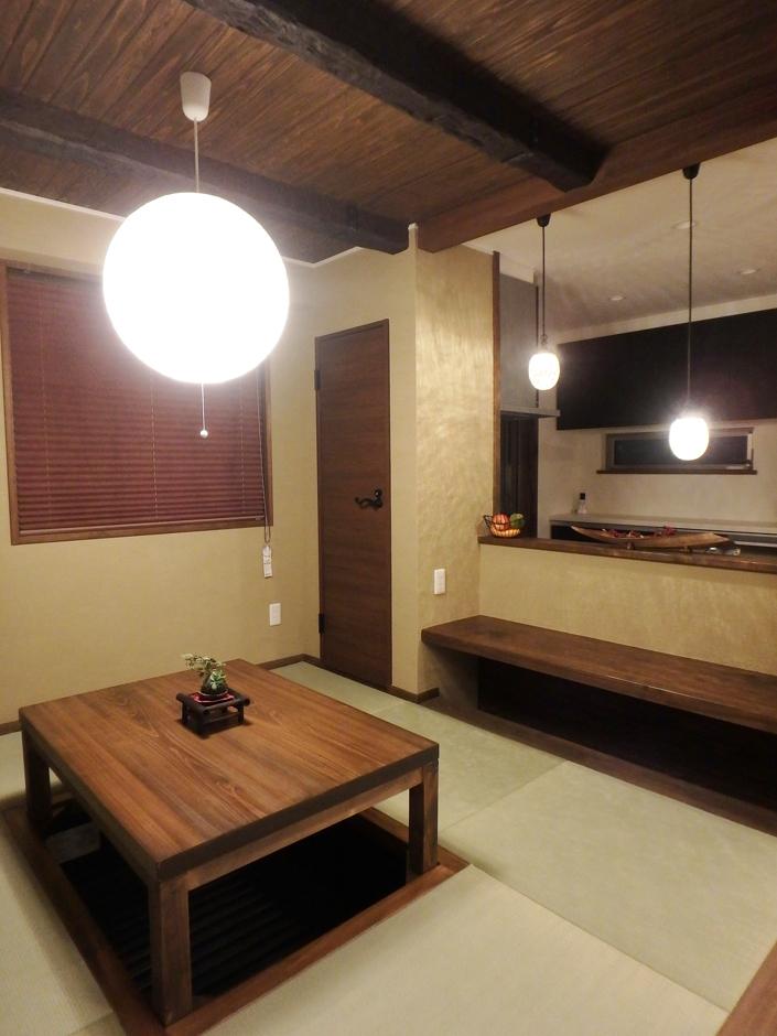 TDホーム静岡西 ウエストンホームズ【和風、自然素材、間取り】照明と畳、掘りごたつと特徴が満載の団らん空間。奥のキッチンでは料理を行う奥さんも団らんを楽しむことができる