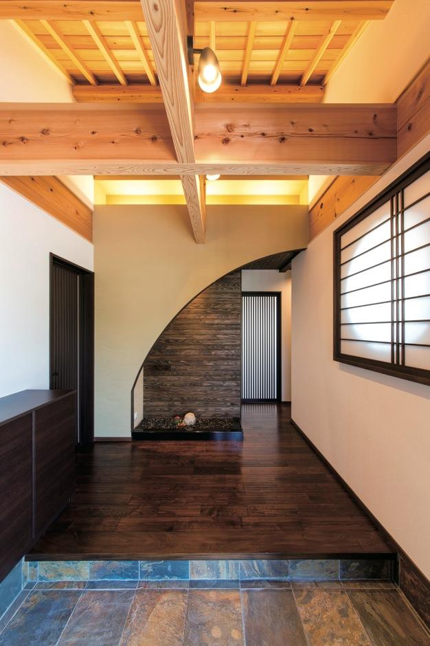 TDホーム静岡西 ウエストンホームズ【和風、自然素材、平屋】壁面に設けた間接照明、立派な梁と勾配天井、アールの垂れ壁の先にある杉のはめ板が印象的。お客様との会話も弾む空間に