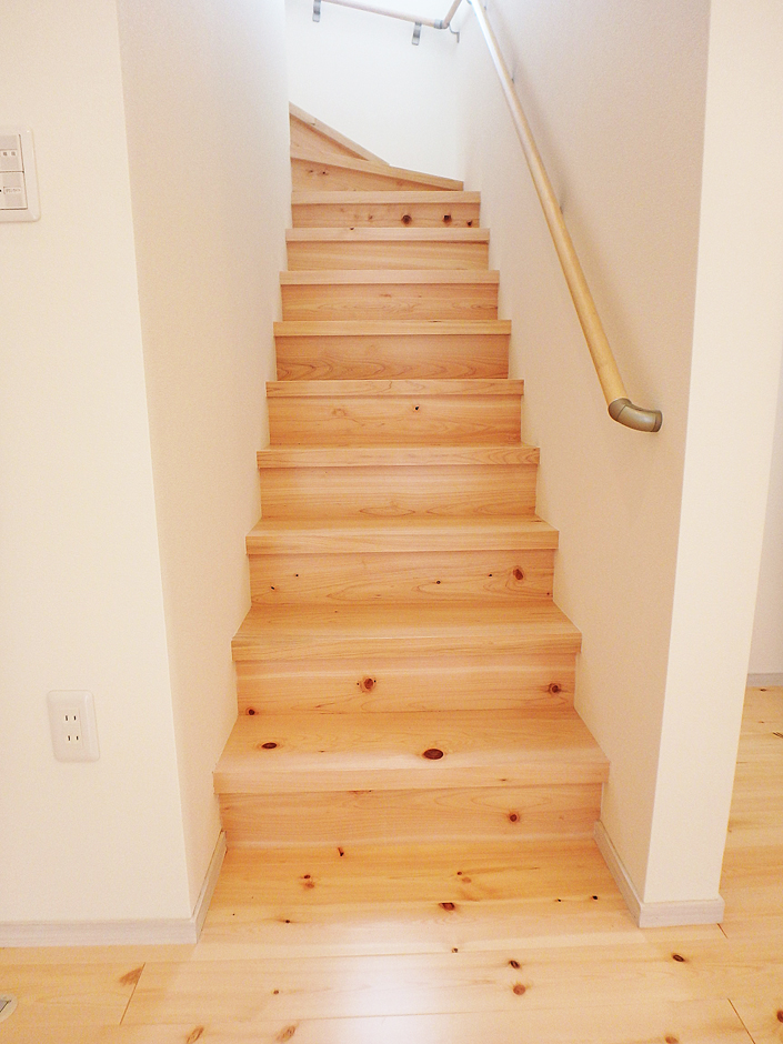 無垢の床が緩やかなカーブの階段に続く。白と無垢が暖かい印象を与える