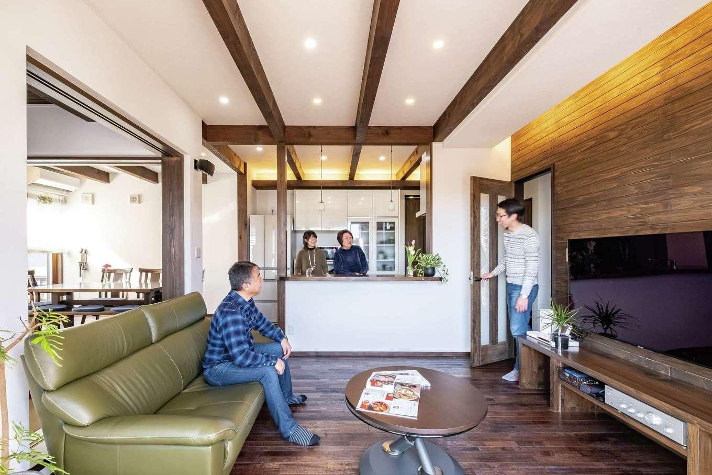 TDホーム静岡西 ウエストンホームズ【デザイン住宅、二世帯住宅、自然素材】つながりを持たせながら緩やかにエリア分けされた20畳のLDKと和室。白い壁に無垢の床と表しの梁が生映え、杉板のテレビステーションがアクセントに