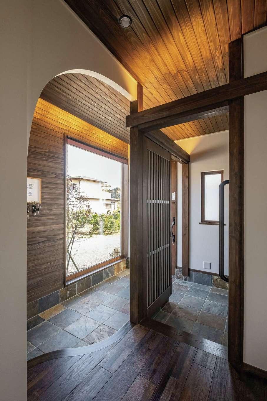TDホーム静岡西 ウエストンホームズ【デザイン住宅、二世帯住宅、自然素材】大きなFIX窓を採用し、圧倒的な開放感を生んだ玄関ホール。夜はヤマボウシと枝垂れ紅葉がライトアップされる。無垢材、天然の錆石、アーチが織りなす和とモダンが共鳴する空間は同社ならでは