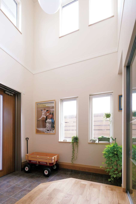 吹き抜けからの光に満たされた玄関。換気システムと組み合わせて吹抜けを設けることで、効率良く家全体を同じ温度に保つ効果が生まれるという利点も