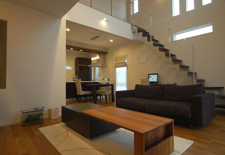 リビングイン階段と吹抜けのあるリビング。広いリビングの後方には2Fへの階段があり、また階段下はパソコン用スペースとして有効活用されている。家具やカーテンは極力色味を抑え、シンプルかつ洗練された空間になっている