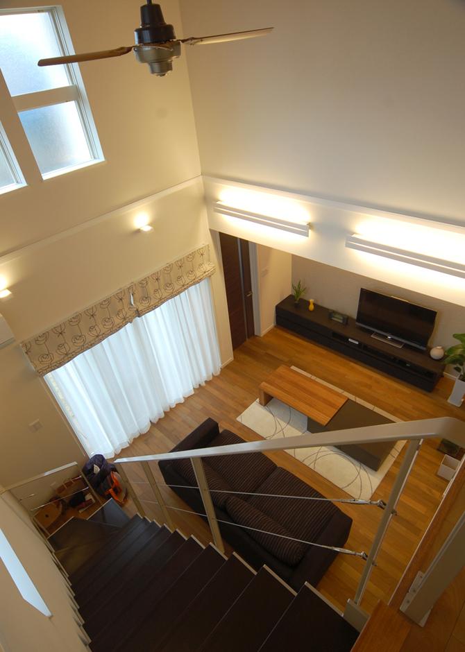 階段上の廊下からは絵になるリビングを見下ろすことができる。シルバーカラーの手すりもモダンな要素の強いアイテム