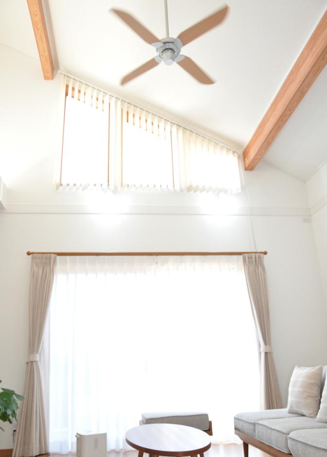 ゆったりとした12畳のこだわりリビング。吹き抜けの勾配天井にはシーリングファンを設置。三連窓からは明るい光が降り注ぐ