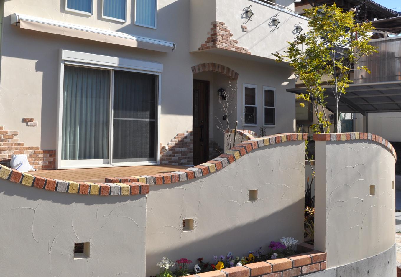 建物とお揃いの可愛らしいレンガ調の壁は足元がミニ花壇になっている