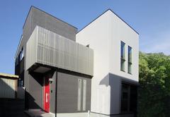 スクエアなシルエットに真っ赤な玄関ドアの二世帯住宅
