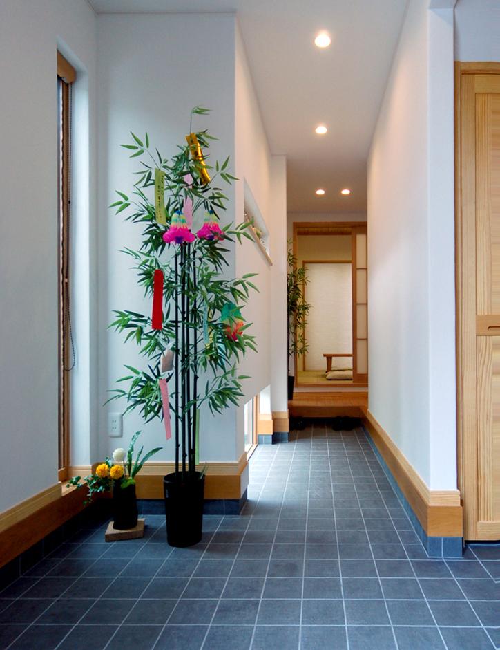 静鉄ホームズ【自然素材、省エネ、間取り】玄関ドアを開けると料亭をイメージした通り土間が。お客さまを誘い込むような通り土間には坪庭が見え、視線の動きをもたらす