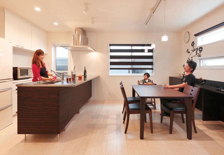 静鉄ホームズ【デザイン住宅、間取り、平屋】ひときわ存在感を放つペニンシュラ型キッチンはLDKの主役。ホワイトを基調とした空間で、暗い木目が引き締め役となり、シルバーの光沢や直線的なフォルムはモダンさに輪をかけている