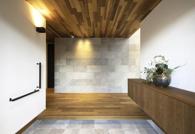 静鉄ホームズ【静岡市駿河区桃園町1-1・モデルハウス】お客様をお迎えする玄関はシンプルながらも素材そのものが持ちあわせる上質さがポイント。正面の壁面に使用した石の壁が、このままリビング空間へと誘う