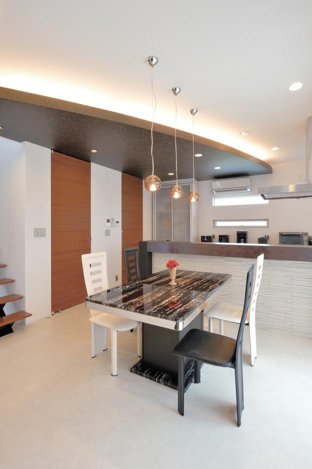 未来創建【デザイン住宅、趣味、インテリア】スタイリッ シュなダイニングキッチンは、ストリップ階段や天井高いっぱいの建具を採用。Rを描く天井は 『未来創建』の提案だった。「私が思い描くイ メージを一回で理解し、期待以上のプランを提案してくれました」