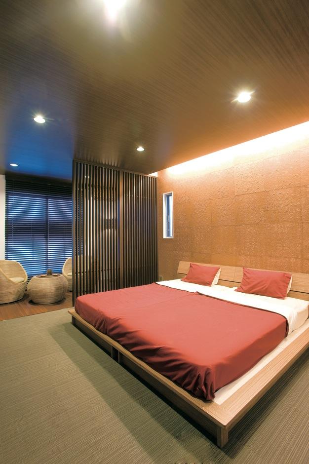 未来創建【デザイン住宅、趣味、インテリア】メインのベッドルームの壁には、何と金色のネパール手漉し紙を使った。間接照明により派手過ぎず、ご夫妻のくつろぎの空間に。このほか、重厚な雰囲気に仕上げたこだわりのオーディオルームもあり、ゆったりと映画や音楽を楽しめる