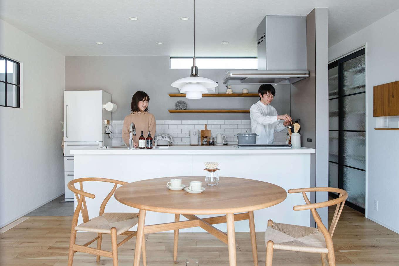 誠一建設 【デザイン住宅、省エネ、間取り】ミーレの食洗機を使いたいという要望があった奥さまは、同製品がオプションに含まれているGURAFTEKTのキッチンをセレクト。アイランド型にしたので夫婦でキッチンにたっても作業がスムーズにできる。背面のタイルや木製の棚は、素材だけでなく高さや位置まで細かくこだわった。パントリーの引き戸は、水回りとの仕切り戸や畳コーナーの室内窓とお揃いのデザイン