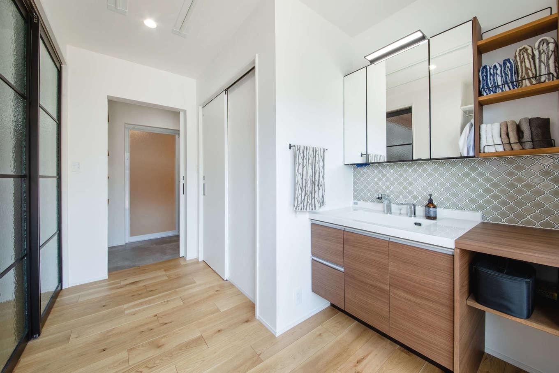 誠一建設 【デザイン住宅、省エネ、間取り】水回りスペースは、洗面とドライルーム&脱衣スペースを引き戸で仕切れるようになっている。ドライルームには室内干し用のポールハンガーを2か所設けてあり、洗濯物をたっぷり干せる。南側にはデッキにつながる掃出窓があり、水回りスペース全体に明るさをもたらしている