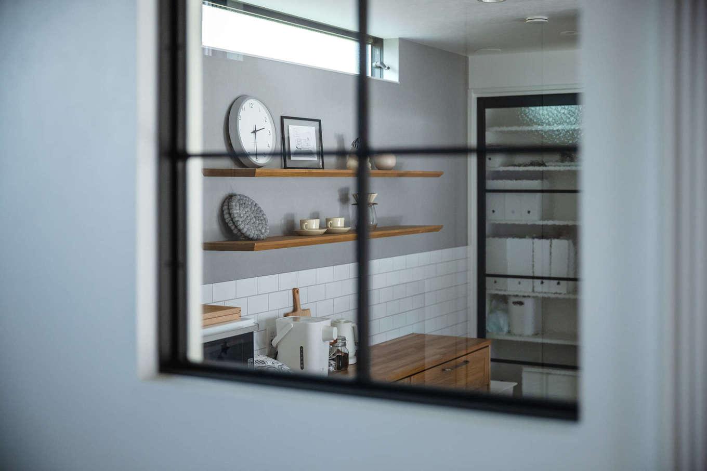 誠一建設 【デザイン住宅、省エネ、間取り】畳コーナーに設けた室内窓からはキッチンの様子が見える。黒いアイアンとデザインガラスの窓は、パントリーの扉や水回りとの仕切り戸と同じデザインで、統一感のあるインテリア空間が実現