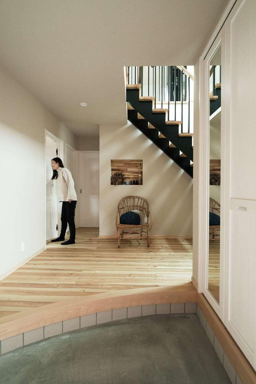ワイズホーム【デザイン住宅、自然素材、省エネ】憧れていた広い玄関。上がりかまちは「直線にする意味はあるの?」というご主人の素朴な疑問からアールを付けた。吹き抜けの鉄骨階段と正面のニッチのバランスも絶妙