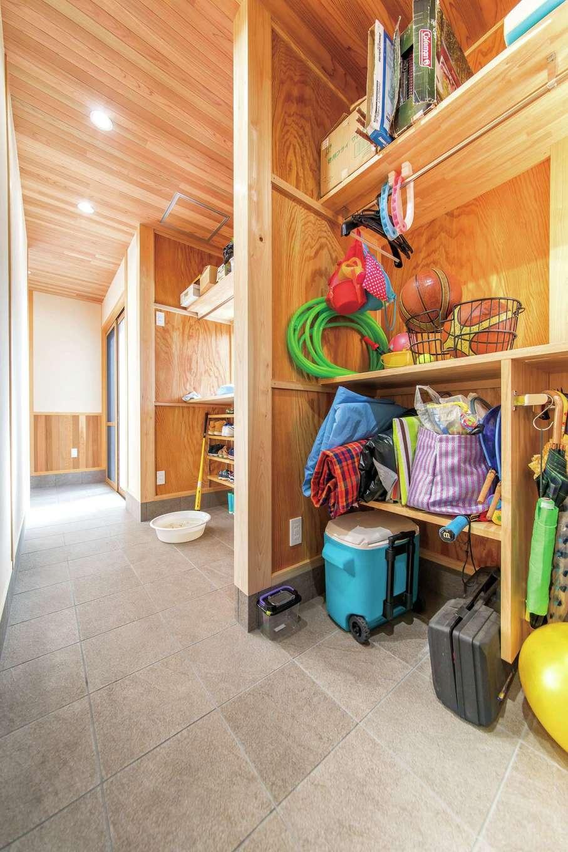 櫻 工務店【和風、自然素材、間取り】玄関を入って左側に位置する大きな土間空間。靴や上着など日常の玄関収納と、キャンプ・アウトドア用品を収納するスペースに分かれており、たっぷり収納できる